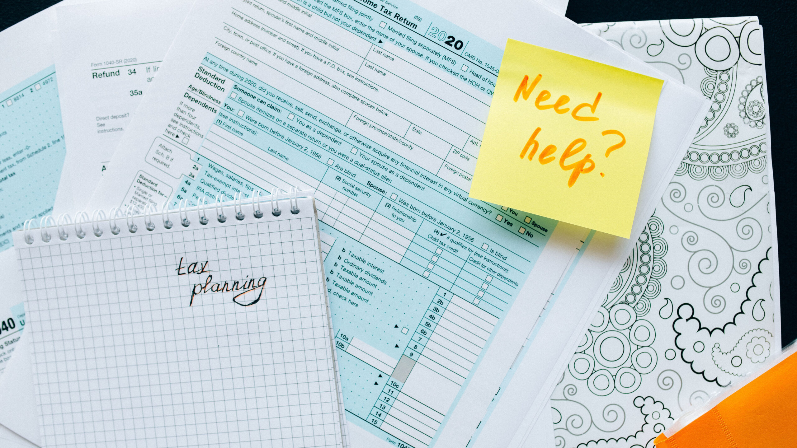 """Canadian tax forms with notes reading """"Need help?"""" and """"Tax planning"""". In the background there is a decorative, paisley doodle."""