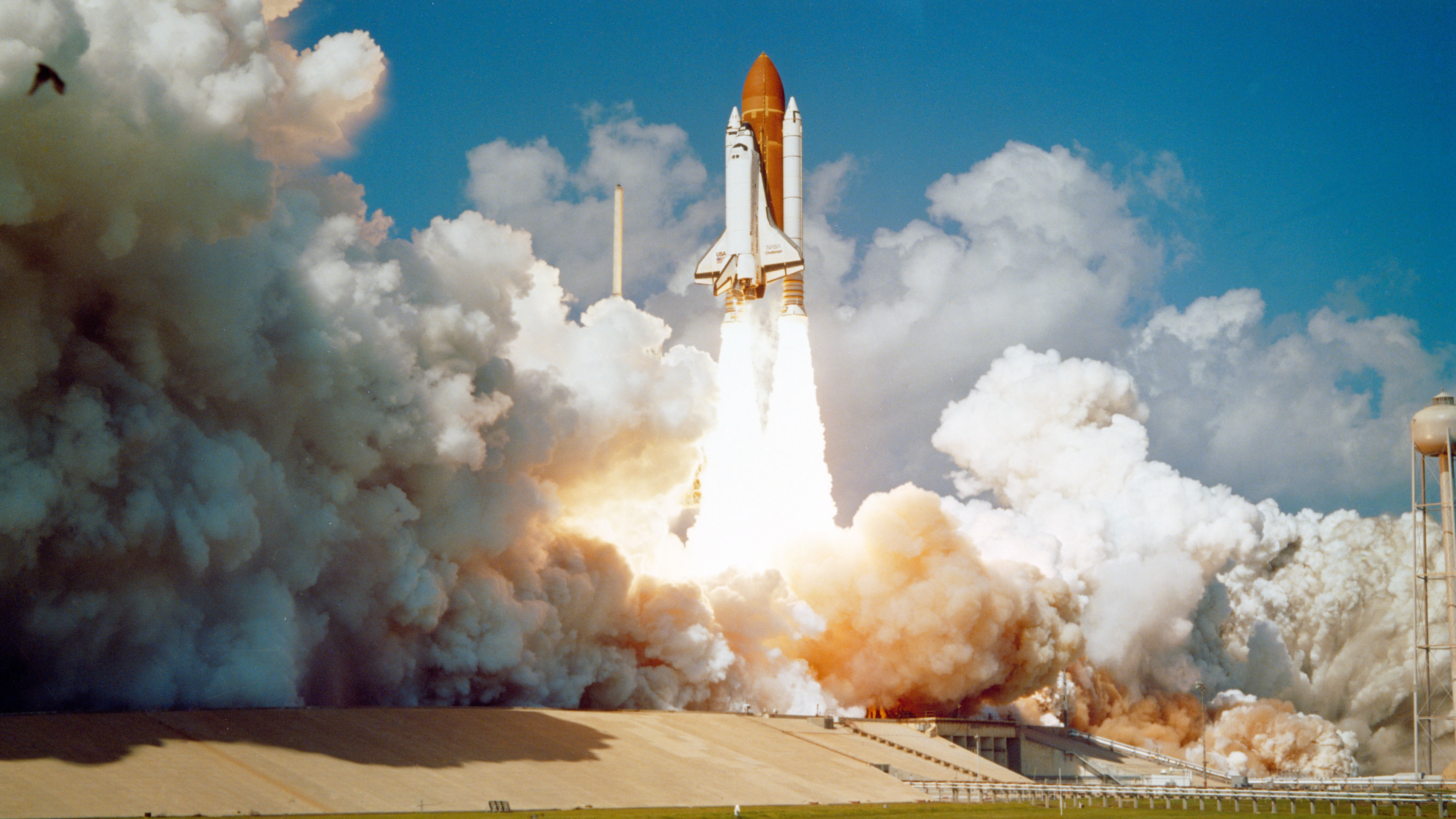 Space shuttle blasts of from Earth. Large plumes of smoke surround launch pad as rocket rises.