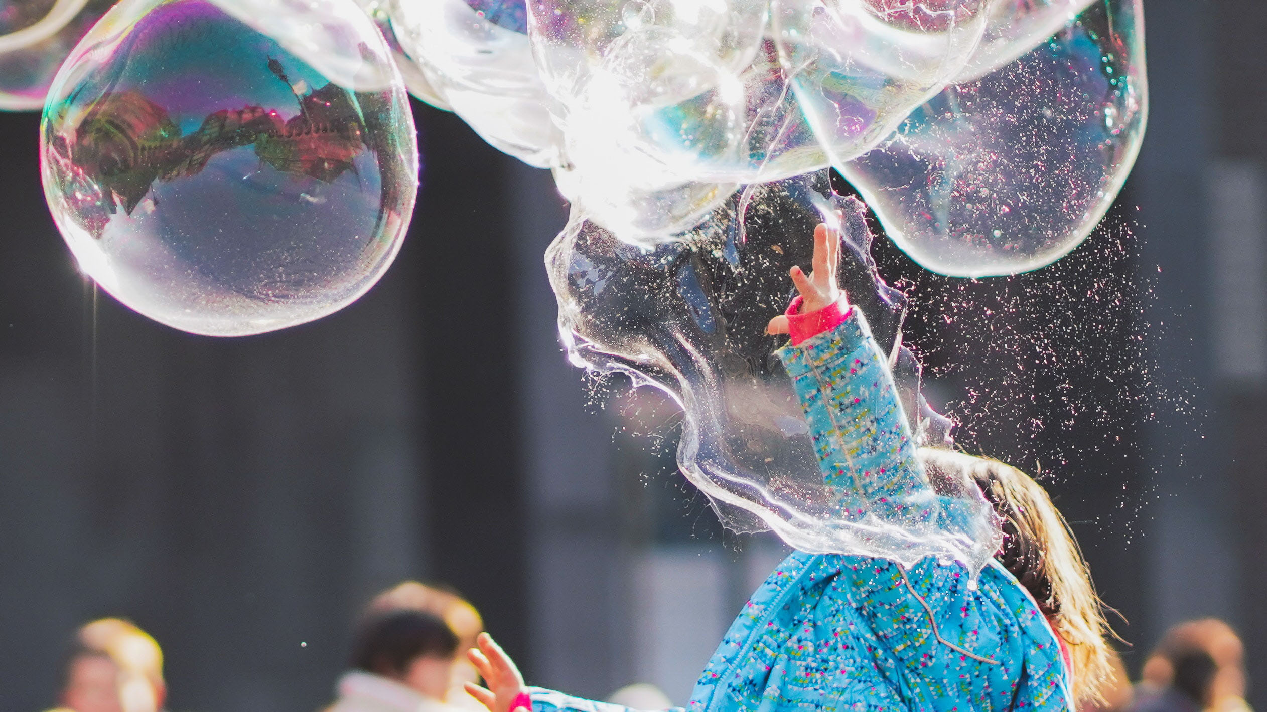 Child in a bright, colourful coat plays with giant bubbles, popping one.