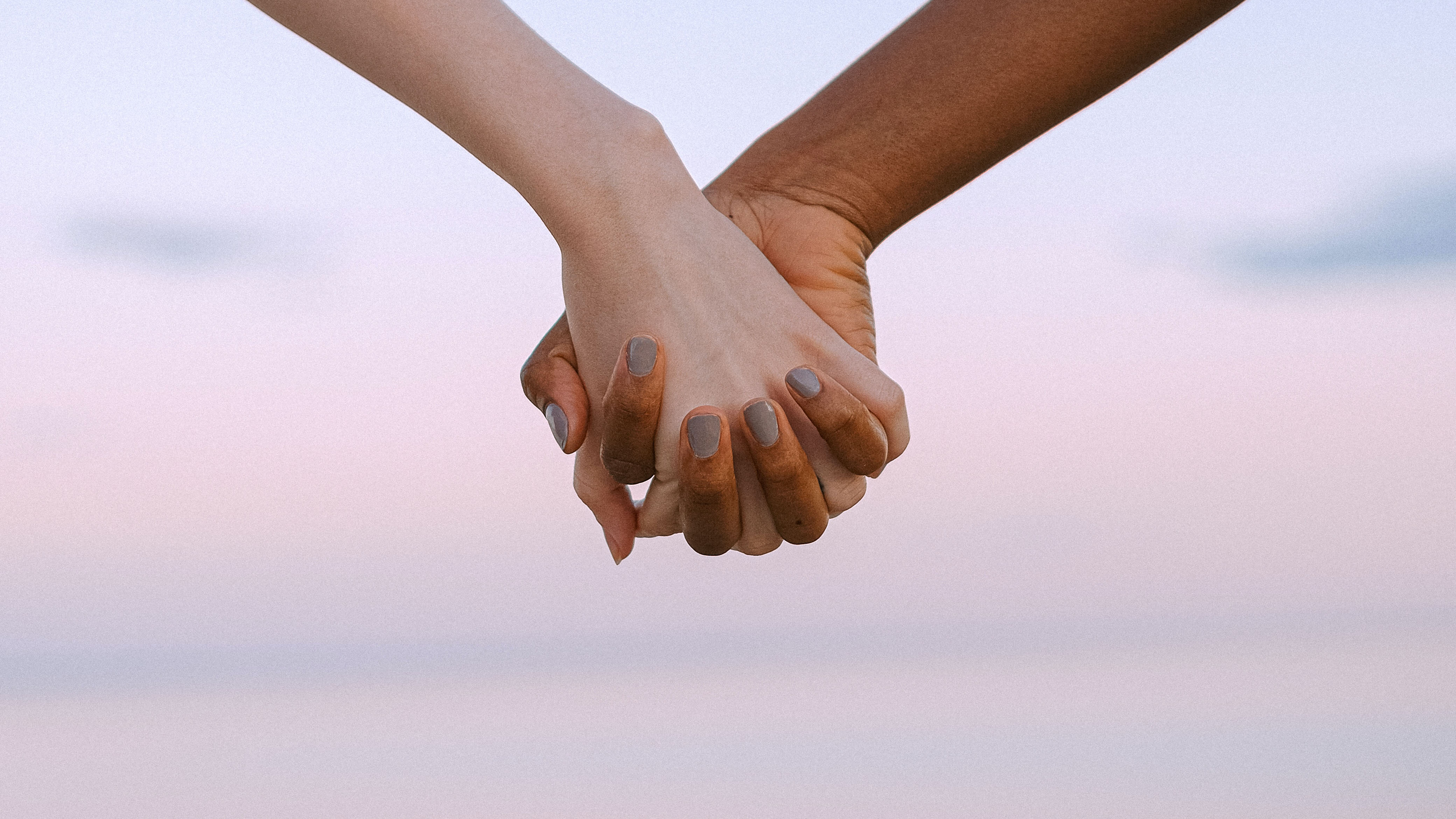 Two people holding hands, only hands in view.