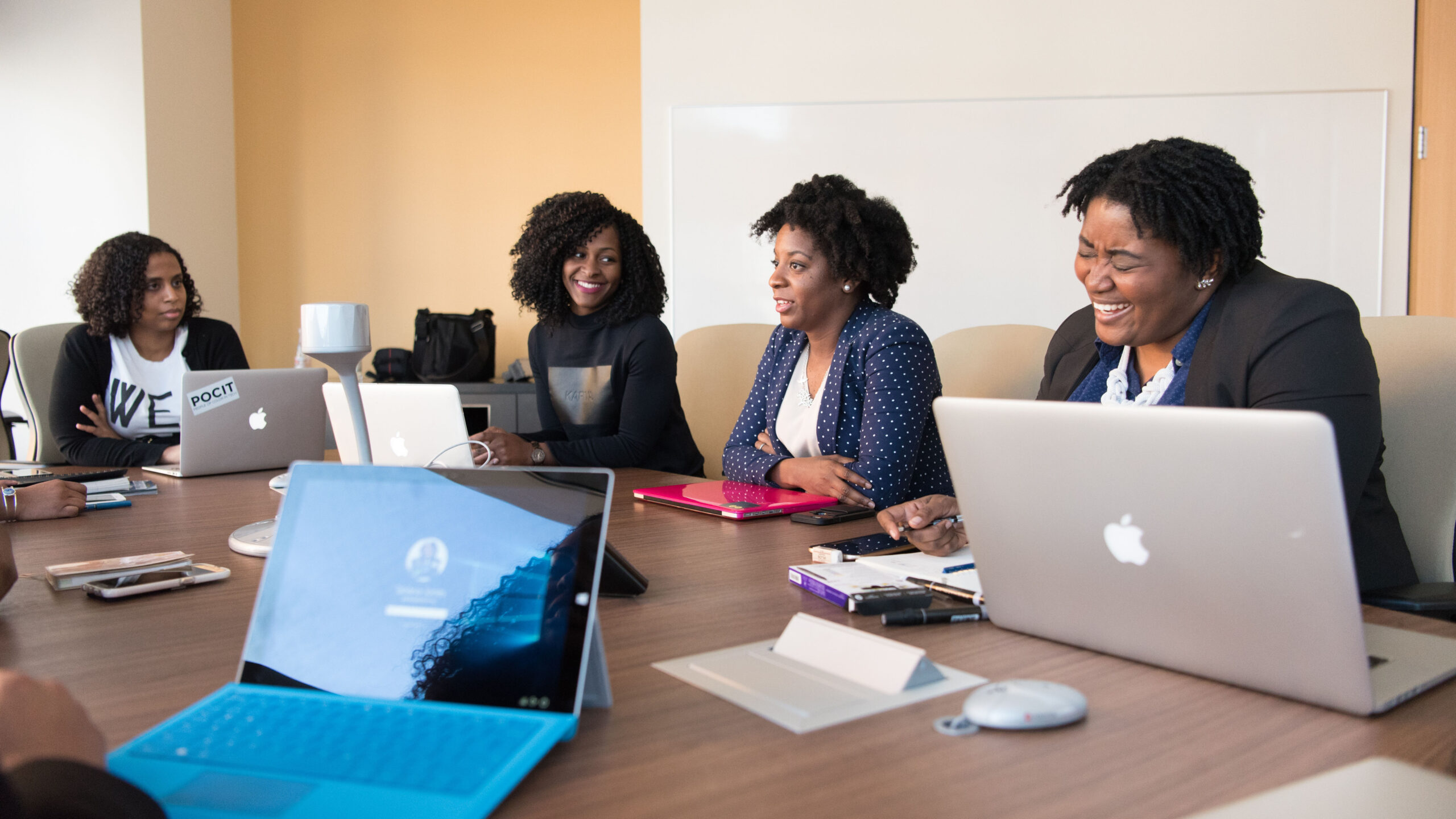Four professional women of colour are at a board table with laptops working.
