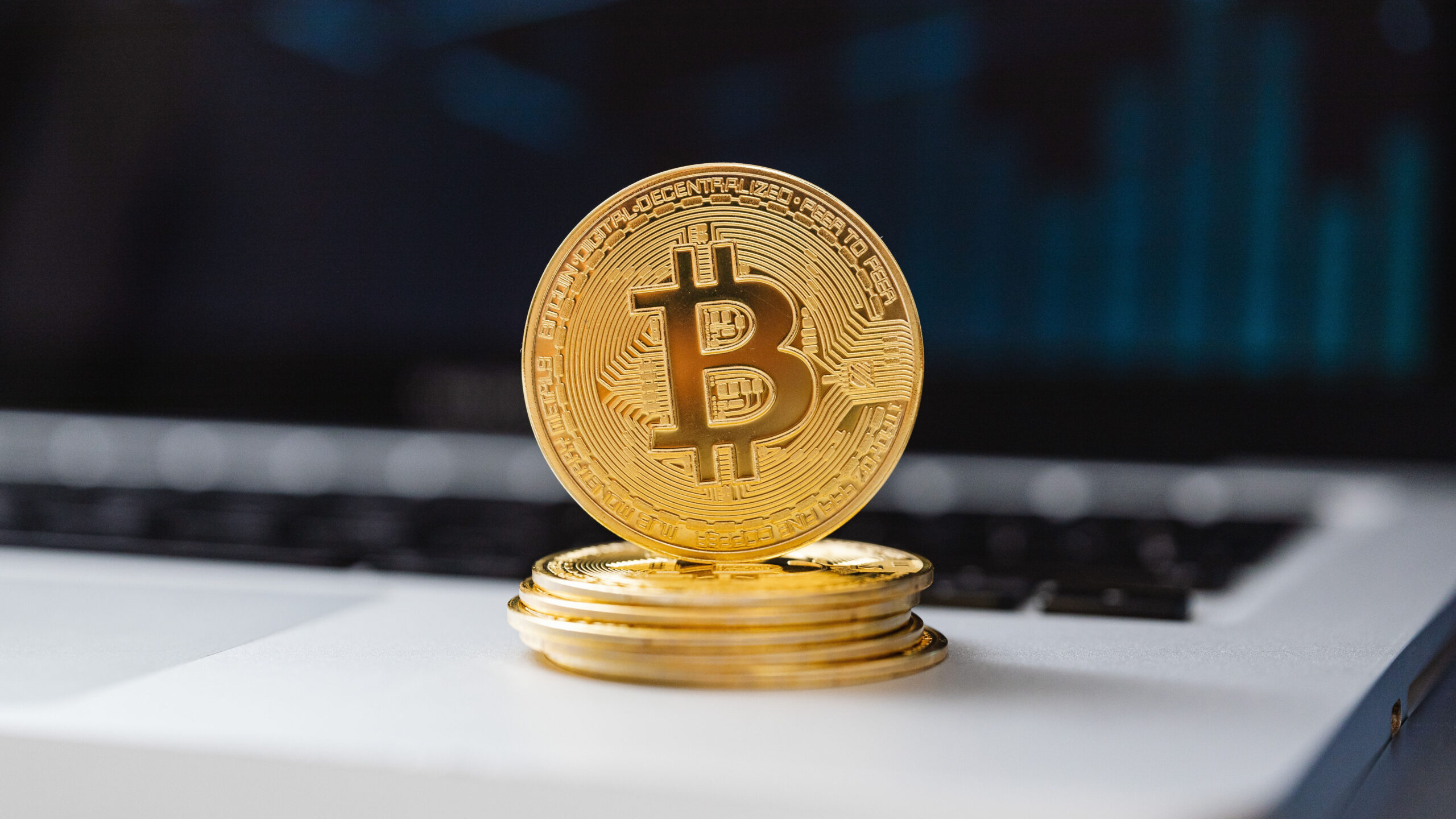 Gold coin with bitcoin symbol is balanced upright on top of a small pile of 5 more coins. The pile appears to be on top of a laptop keyboard.