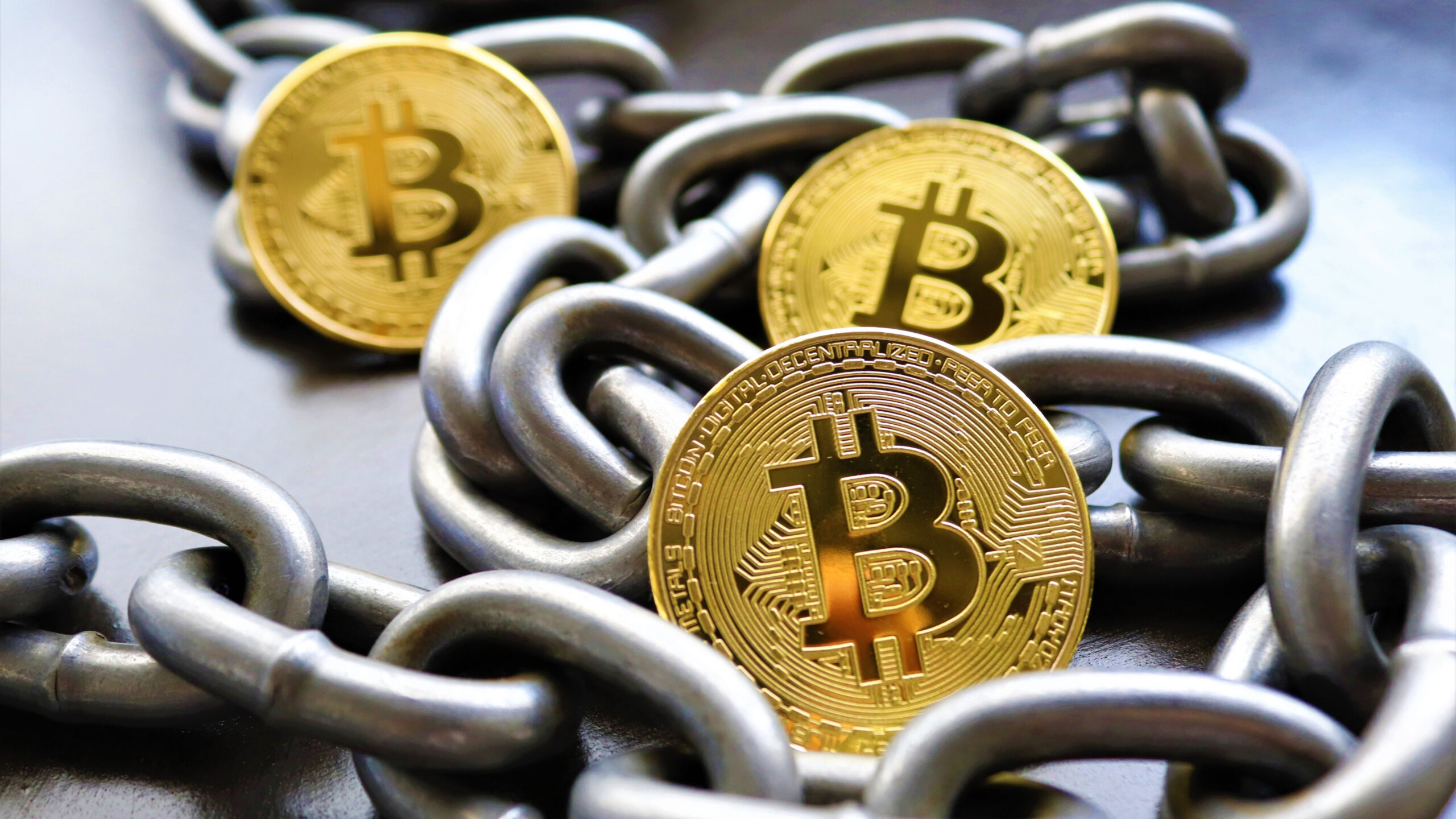three gold coins, with bitcoin symbol, placed among iron chains.