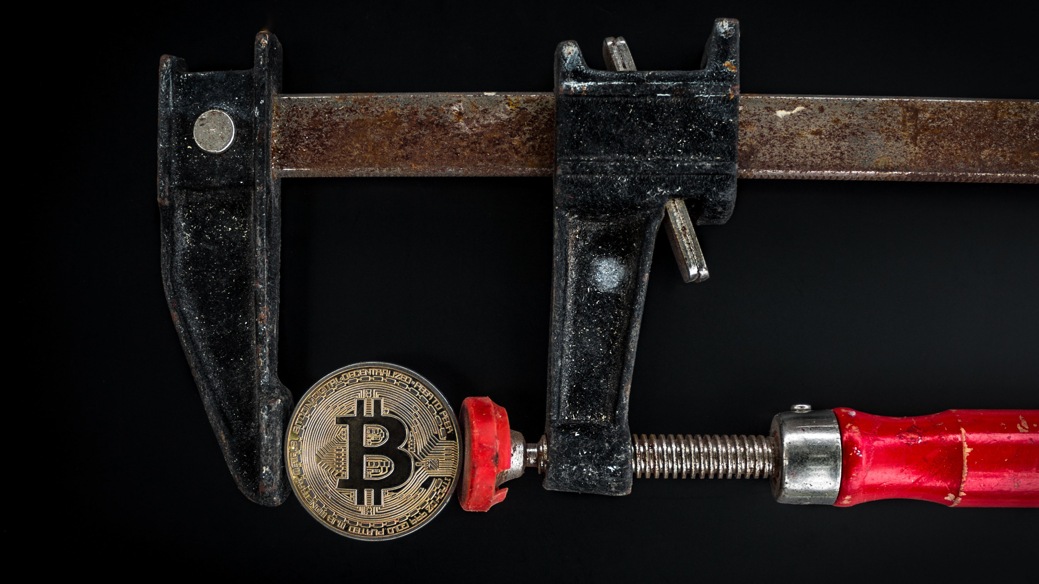 A coin with bitcoin symbol held in a vice.