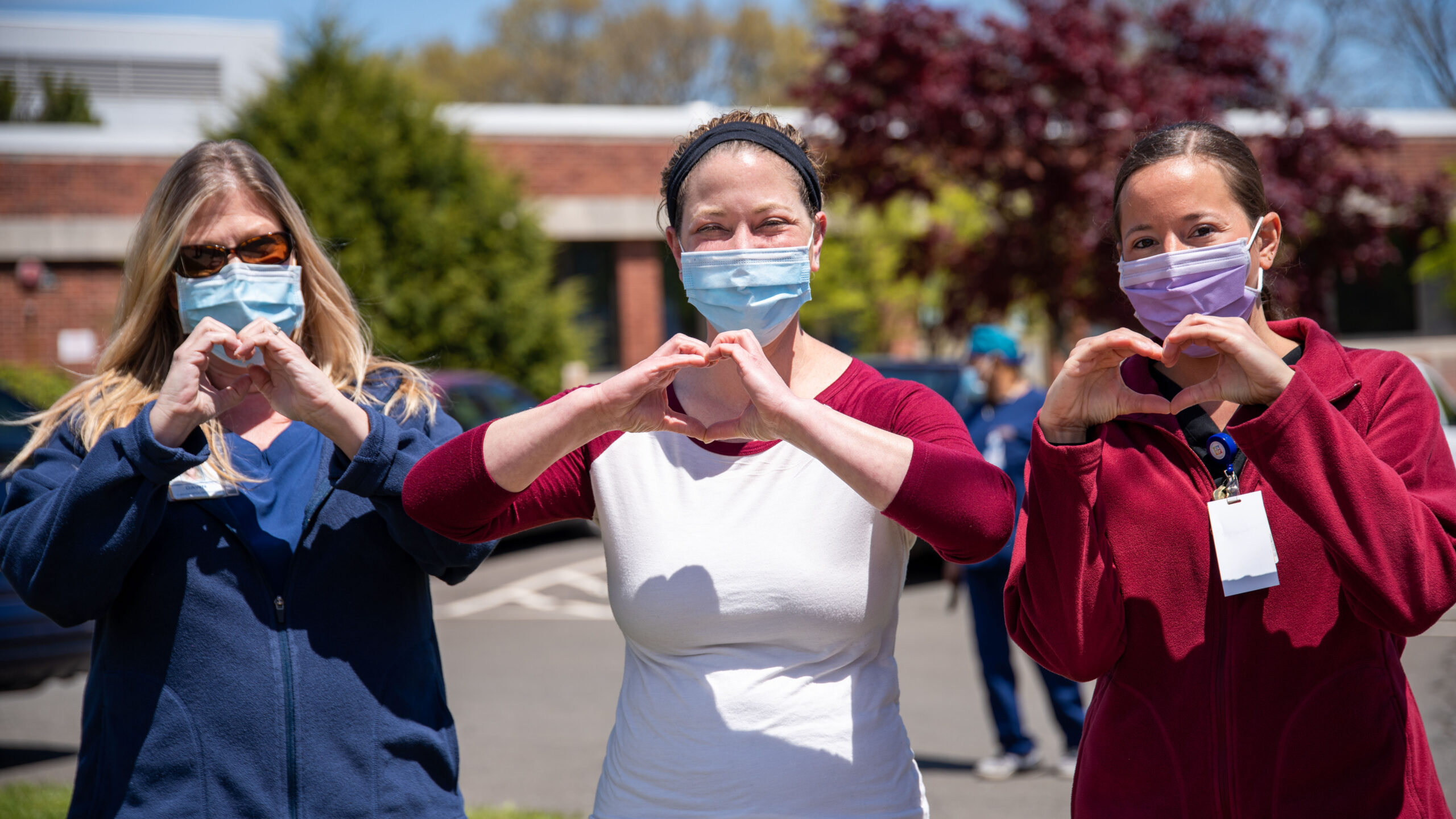 Three women stand together outdoors. They are wearing medical masks and face the camera, holding the hands in heart shapes towards the camera.