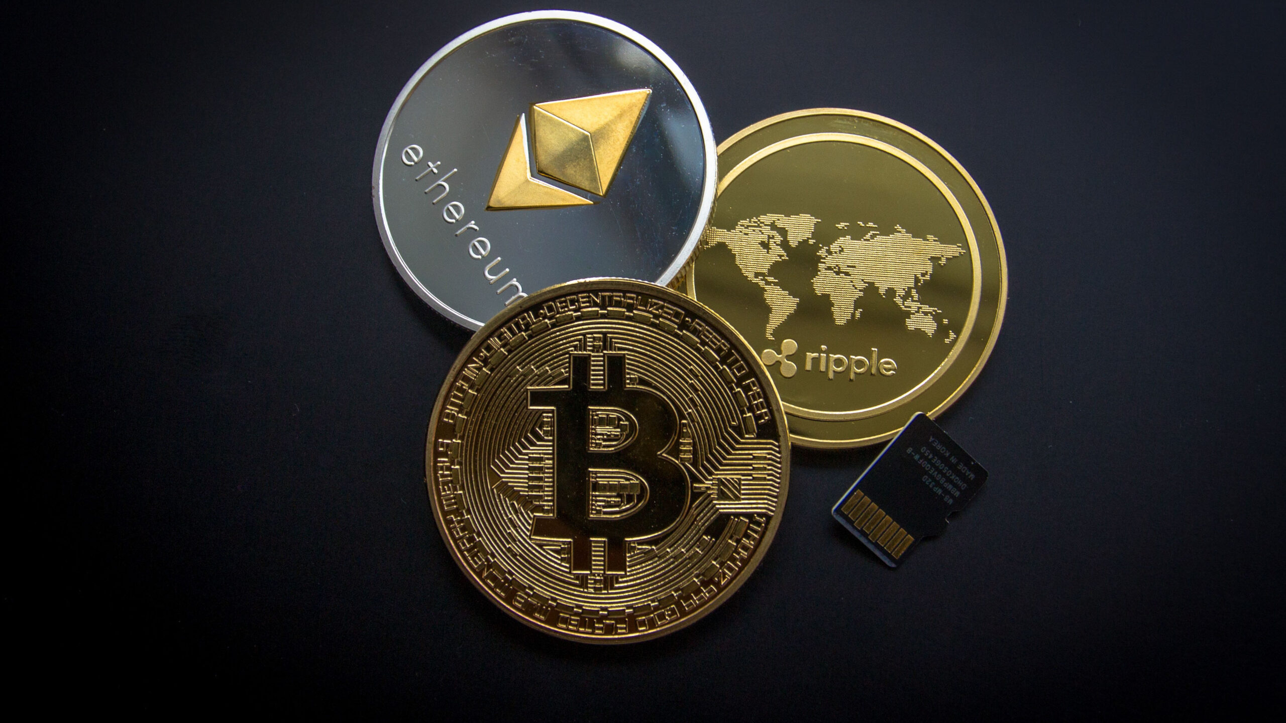Three coins with different cryptocurrency symbols accompanies by SD card.