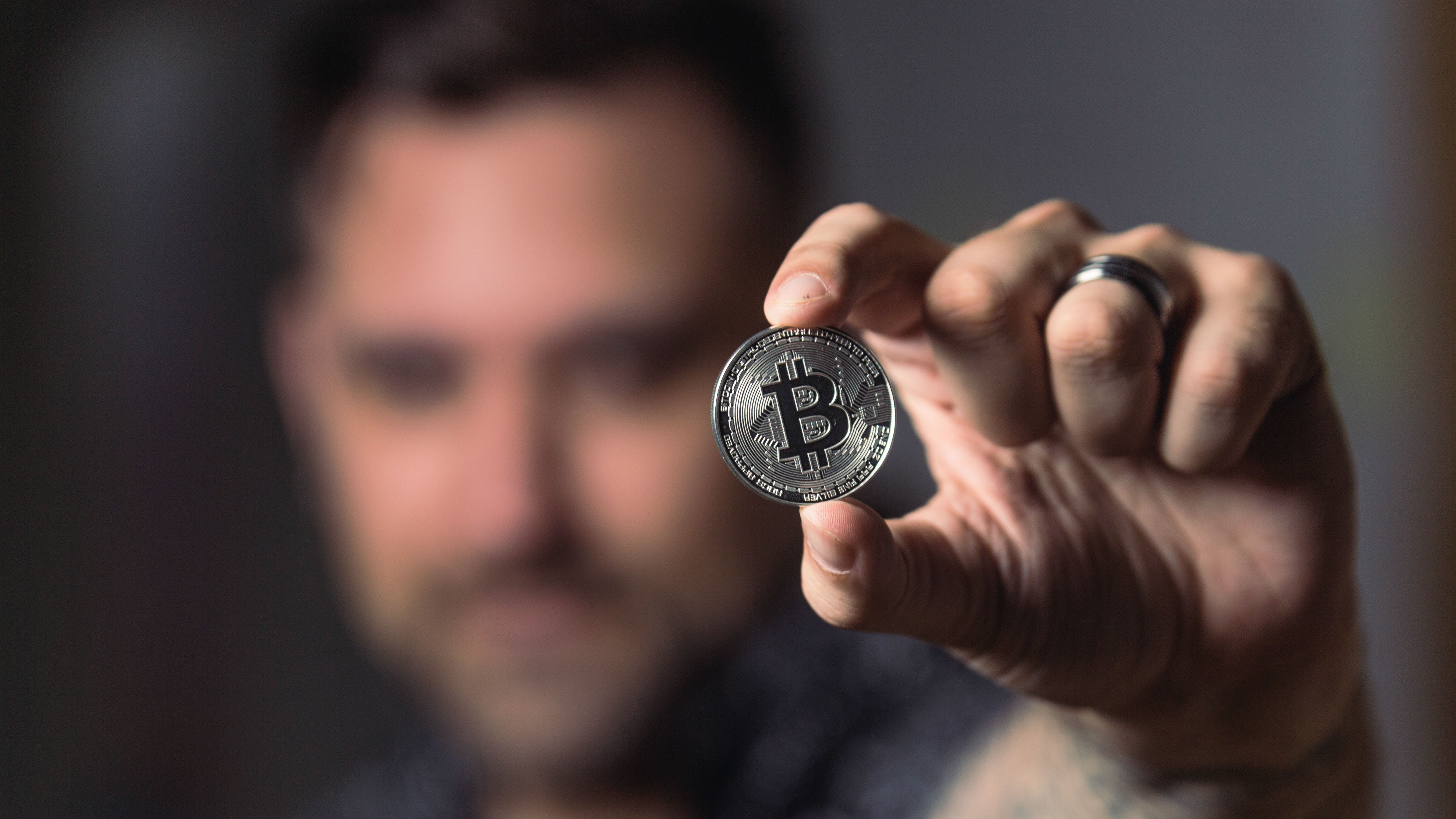 Man holds out silver coin with bitcoin symbol, he is blurred in the background.