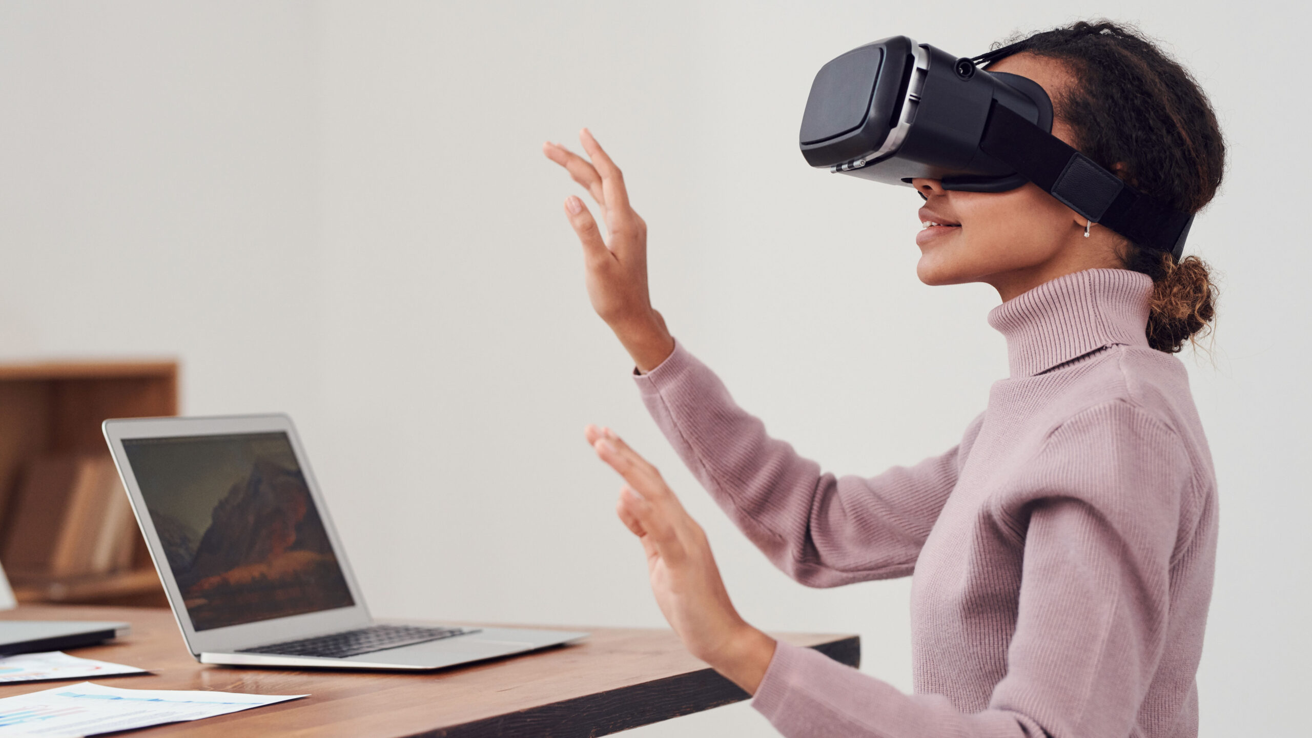 Woman sits at laptop on desk wearing VR headset. Her arms are raised and she smiles.