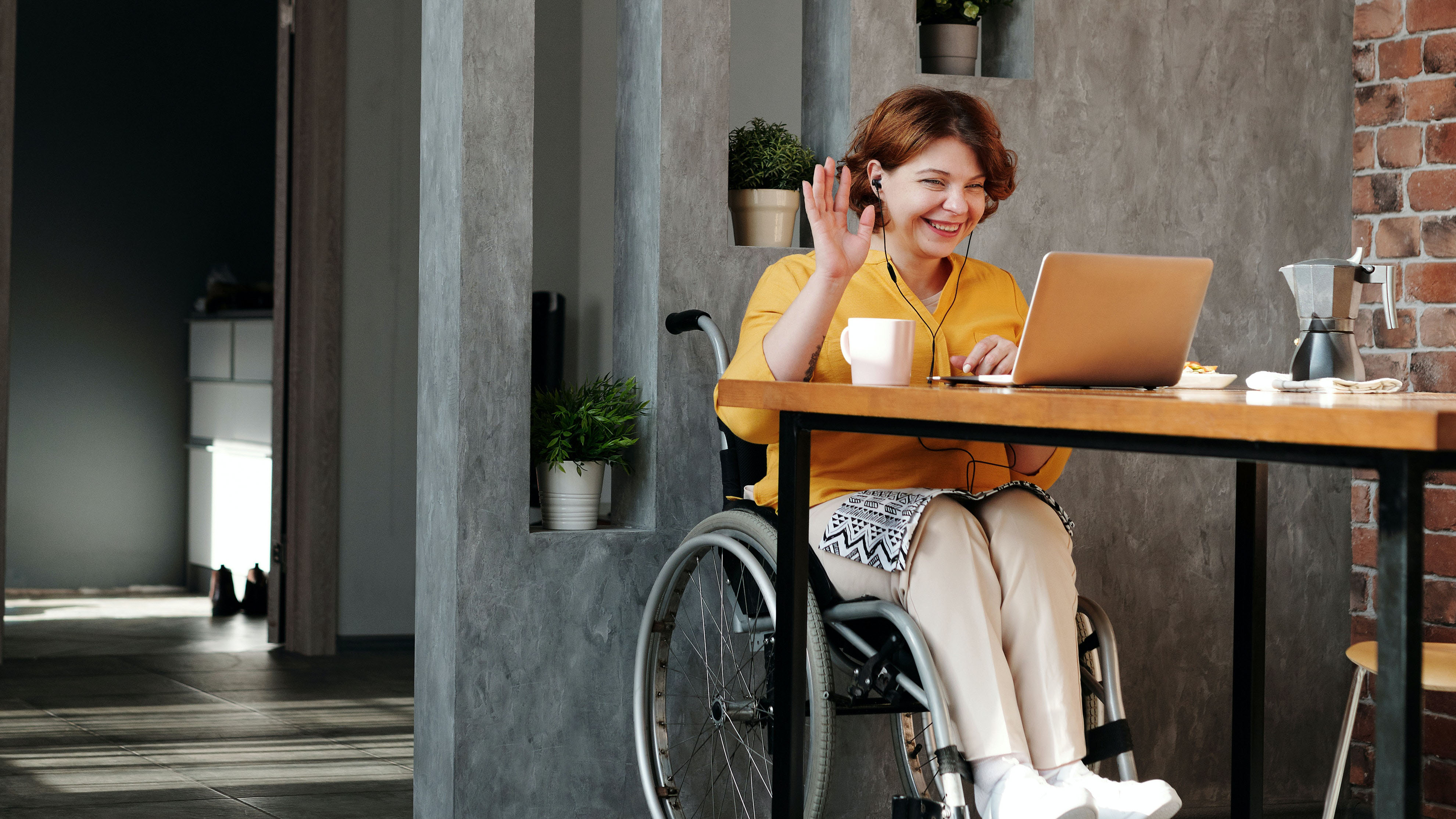 Woman in wheelchair sits at desk. She is at a laptop having a video call, smiling and waving.