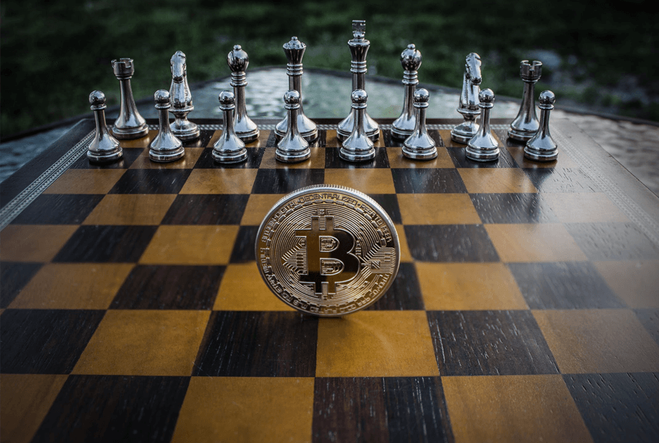 Chess board with silver pieces and bitcoin balanced on centre line.