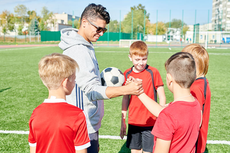 Young man coaches youth soccer team.