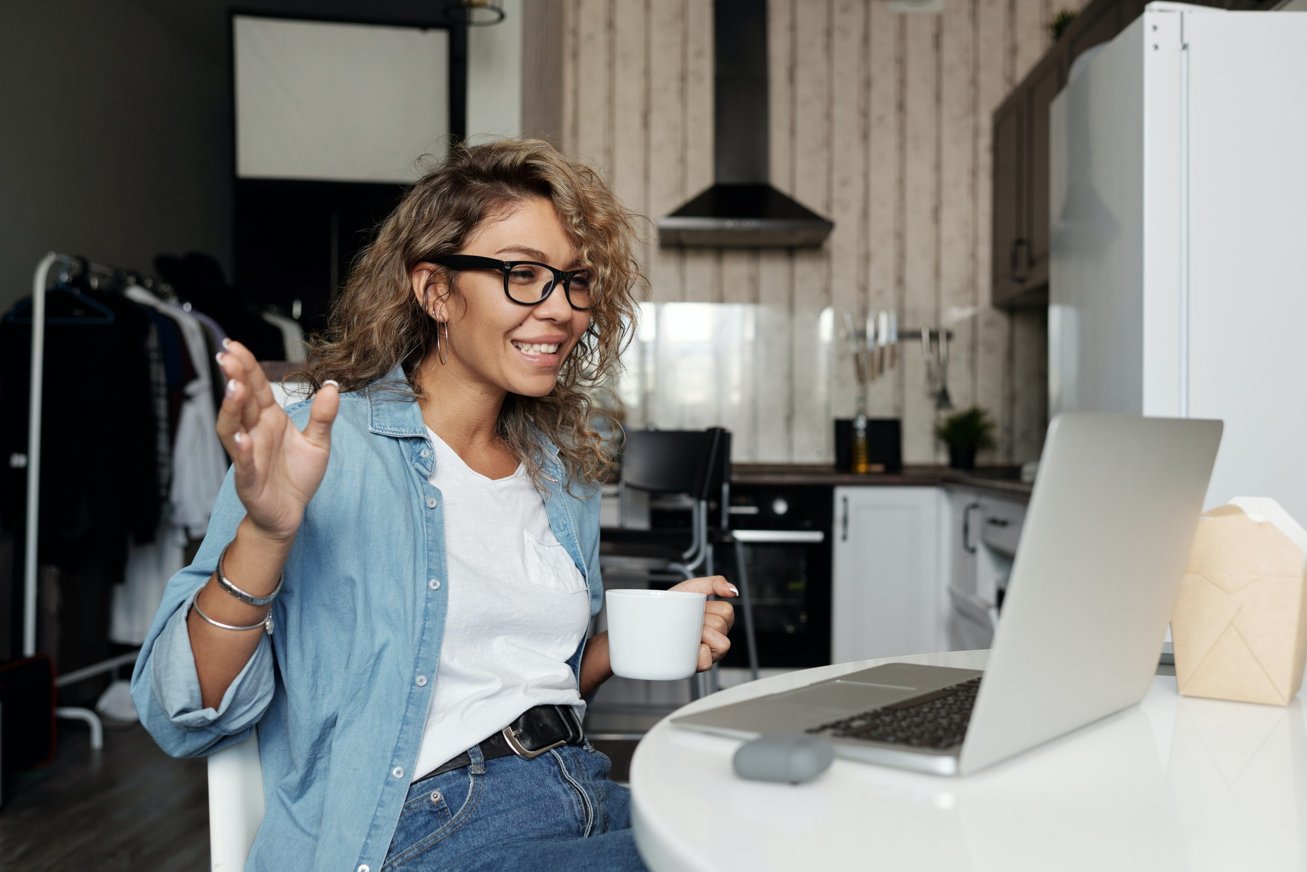 Young woman at laptop in video meeting smiles and holds her coffee.